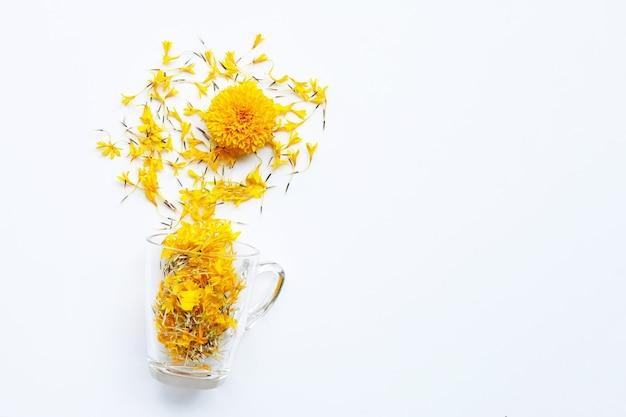マリーゴールドの花びらが付いたガラスのカップ。花のハーブティーのコンセプト。