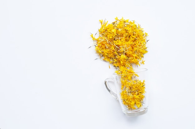 白い背景にマリーゴールドの花びらが付いたガラスのカップ。花のハーブティーのコンセプト。