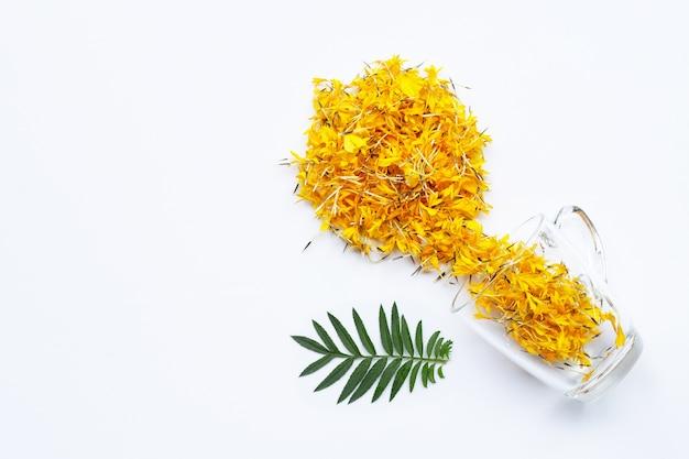 白い花のハーブティーのコンセプトにマリーゴールドの花びらが付いたガラスのカップ。