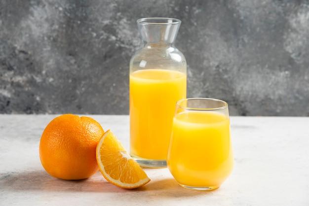 Стеклянные чашки свежего сока с дольками апельсина.