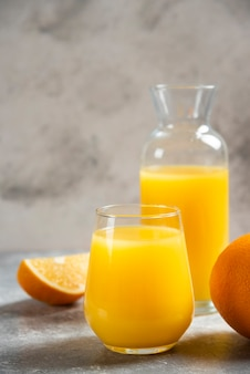 Стеклянные чашки апельсинового сока и дольки апельсина.