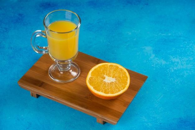 木の板にオレンジジュースのガラスカップ。