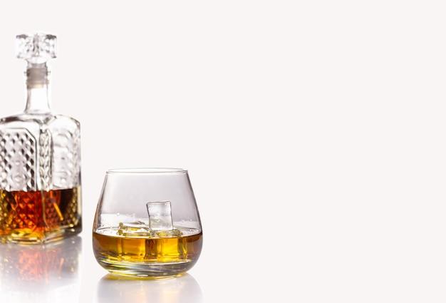 Стеклянный графин, наполовину наполненный коньяком или другим алкогольным напитком, и стакан с изолированным льдом