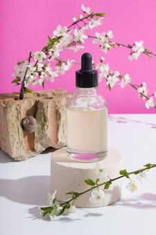 연단에 있는 유리 점적기 병에는 분홍색 배경에 나뭇가지가 피어 있습니다. 세로 스톡 사진
