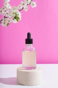 Стеклянная бутылка-капельница на подиуме с цветущими веточками на розовой поверхности