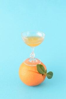Стакан, наполненный апельсиновым соком, стоит на апельсине, у которого также есть зеленые листья на синем фоне. летний освежающий цитрусовый напиток с креативной идеей.