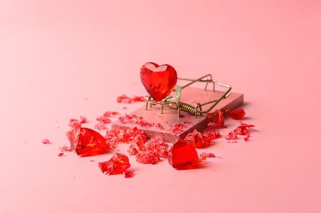 분홍색 배경에 쥐덫에 있는 유리 심장. 발렌타인 데이를 위한 창의적인 컨셉입니다.