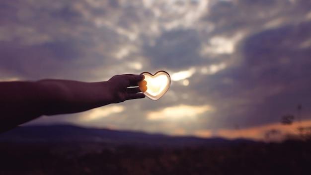 曇った薄明の空の上に太陽が入ったガラスのハート