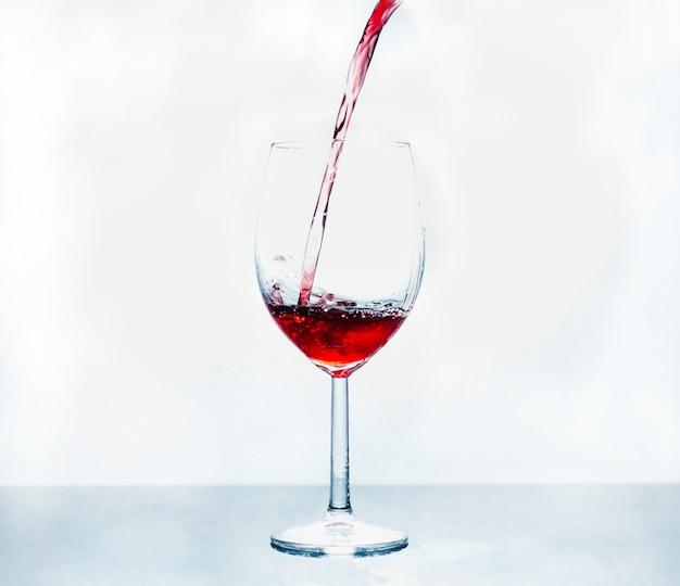 Стакан, в который наливают красное вино на абстрактный фон.