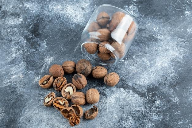 Стеклянная банка, полная здоровых грецких орехов на серой поверхности.
