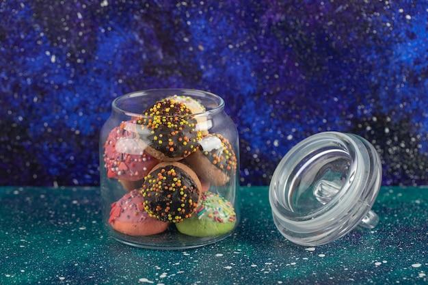 작은 다채로운 도넛으로 가득 찬 유리 병.
