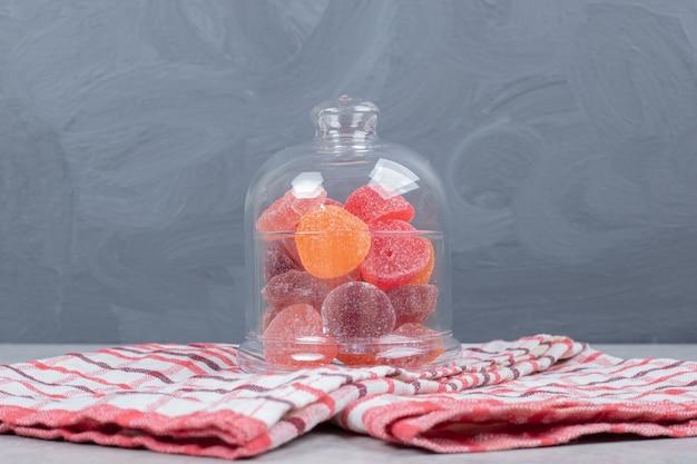 赤いテーブルクロスに甘いお菓子のガラス瓶。