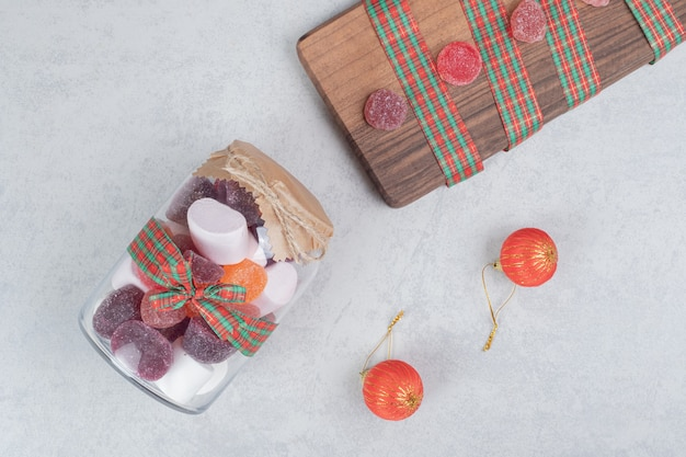 木の板に甘いお菓子のガラス瓶。高品質の写真
