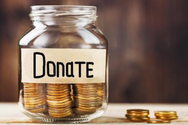 동전과 비문 기부와 함께 유리 항아리