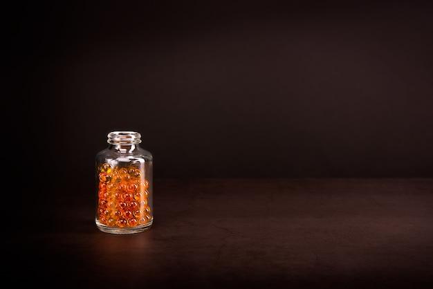 茶色の背景に明るいオレンジ黄色の錠剤が入ったガラス瓶