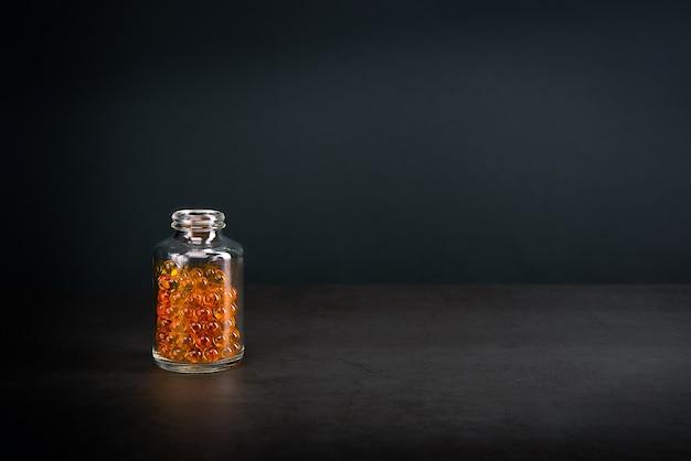 灰色の背景に明るいオレンジ黄色の錠剤が入ったガラス瓶