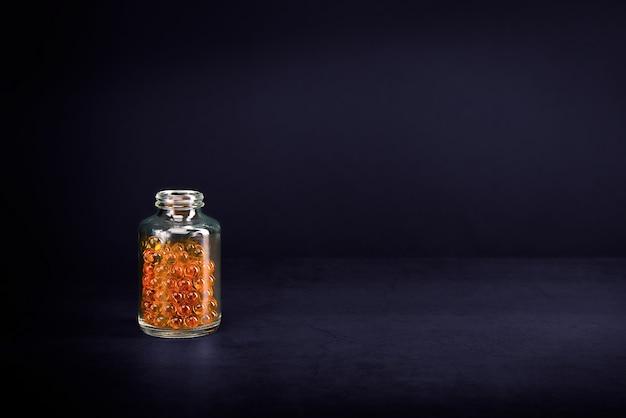 紫色の背景に明るいオレンジ黄色の錠剤が入ったガラスの瓶。