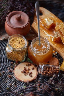 木の板の上に花粉、蜂蜜、プロポリスが入ったガラスの瓶が籐のテーブルの上に立っています