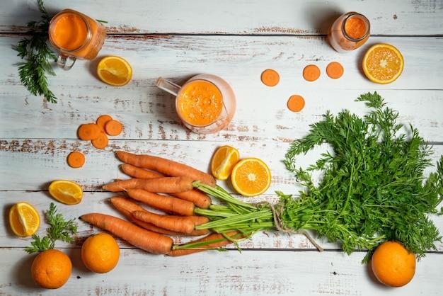 ガラスの水差しとにんじんオレンジとにんじんといくつかのオレンジの天然ジュースが入ったボトル