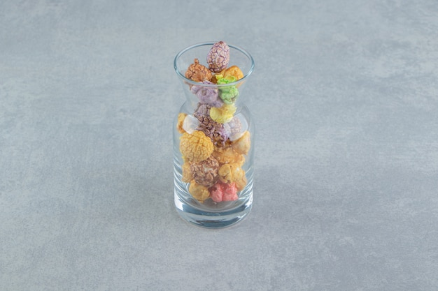 甘い色とりどりのポップコーンのガラスの水差し。