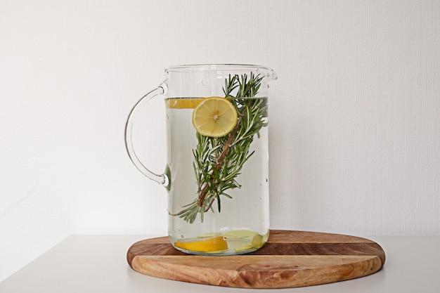 白い背景の上の木製のまな板にレモンとローズマリーと水のガラスの水差し