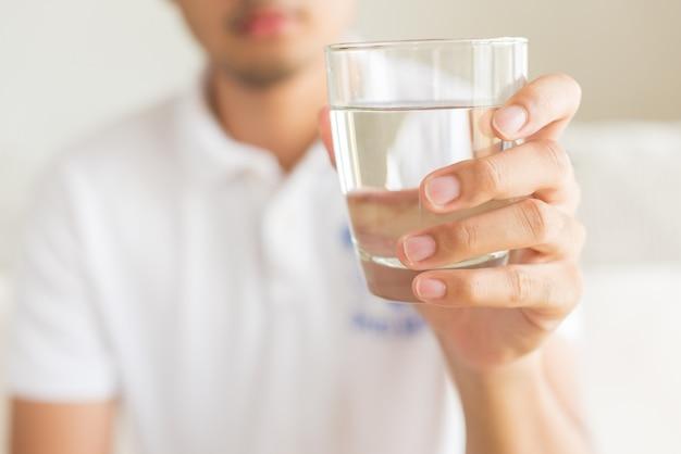 Стеклянная минеральная вода в руках человека. концепция здорового напитка.