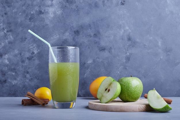 Стакан яблочного сока с корицей и фруктами.
