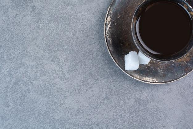 灰色のテーブルにアロマダークティーのグラス。