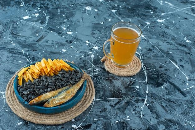 青いテーブルの上にある、トリベットの木製プレートにビールと前菜を一杯。