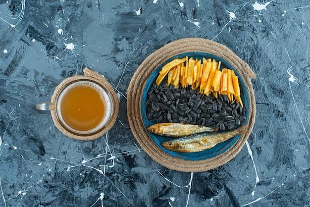 파랑에 삼발이에 나무 접시에 맥주와 전채의 유리.