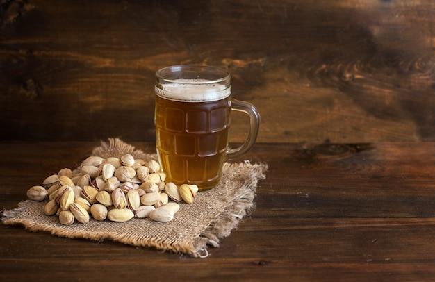Стакан пива и фисташек на темном деревянном фоне
