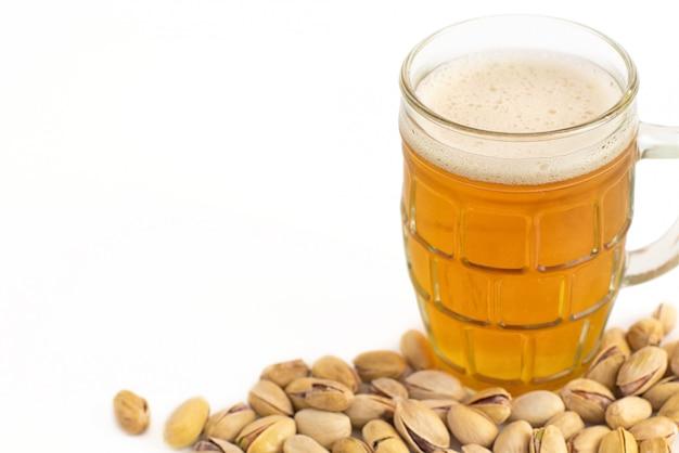 Стакан пива и фисташек на белом фоне