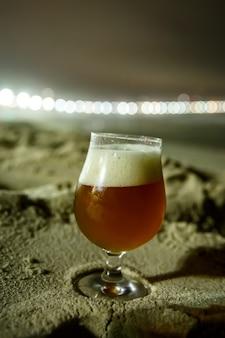 Стакан пива на пляже копакабана в рио-де-жанейро, бразилия. ночное освещение.
