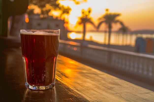 바에서 맥주 한 잔. 바다의 일몰