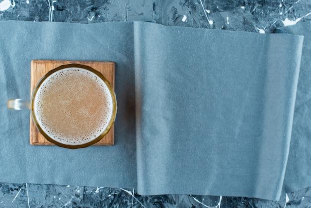 Стакан пива на доске на кусках ткани, на синем столе.