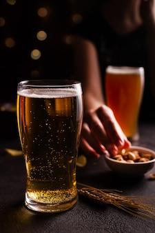 테이블에 맥주 한 잔. 간식을 먹는 여자