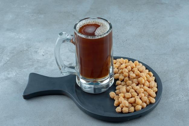 어두운 커팅 보드에 완두콩과 맥주 한 잔. 고품질 사진