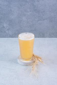 白い表面に小麦とビールのガラス