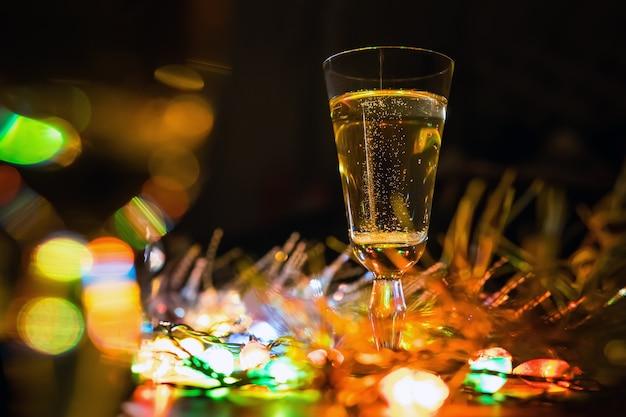 크리스마스 장식에 테이블에 샴페인 한 잔. 크리스마스의 축 하입니다. 와인 잔에 반사된 전기 색 조명