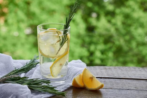 緑の葉の背景に冷やしたレモネード、レモンウェッジのガラス