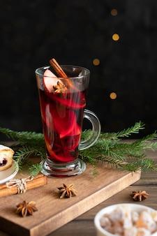 Бокал рождественского глинтвейна со специями и ягодный пирог