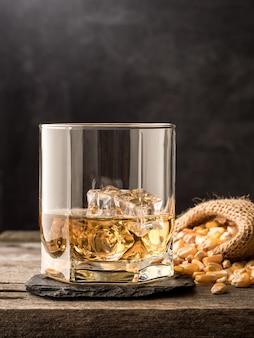 Стакан классического кукурузного виски (бурбона) на деревянном столе с семенами кукурузы на столе. скопируйте пространство.