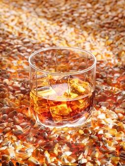 Стакан классического кукурузного виски (бурбона) стоит на светящихся кукурузных семенах. вертикальное фото, копировать пространство.