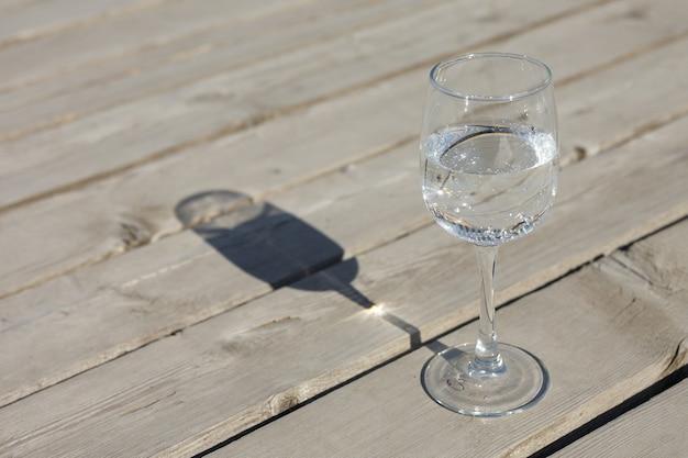 깨끗한 탄산수 한 잔이 오래된 판자에서 회색 나무 바닥에 선다. 미네랄 탄산수의 장점.