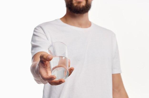 Стакан чистой воды в руке мужчина в обрезанной светлой рубашке. фото высокого качества