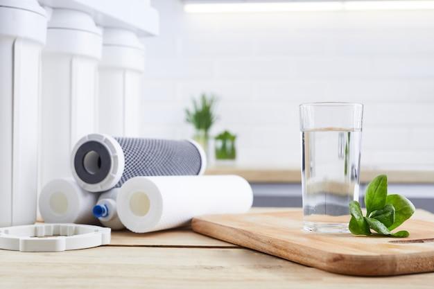 Стакан чистой воды с осмосным фильтром, зелеными листьями и картриджами на деревянном столе в кухонном интерьере