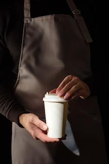 バリスタの手にコーヒーのグラス