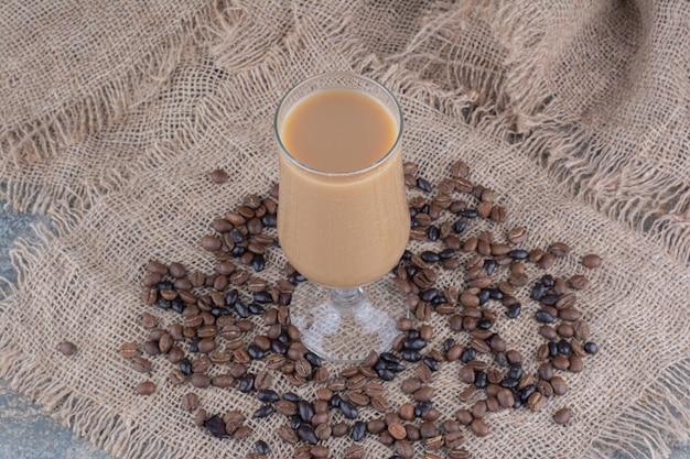 대리석 백그라운드에 원두 커피와 커피 한 잔. 고품질 사진