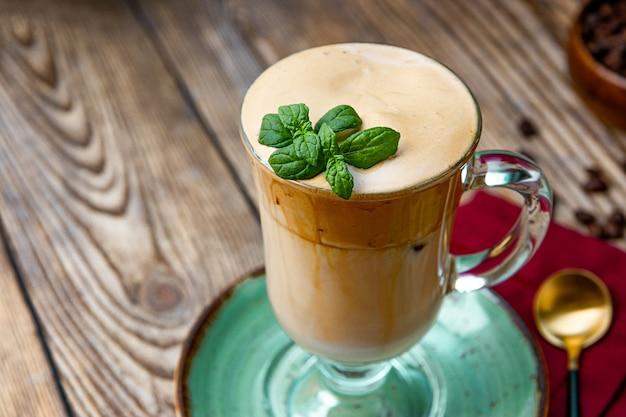 テーブルの上のミントの葉で飾られたミルクとコーヒーのグラス、ダルゴナコーヒー、クローズアップ。