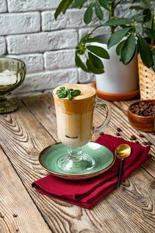 テーブルの上のミントの葉で飾られたミルクとコーヒーのグラス、ダルゴナコーヒー、縦の写真。